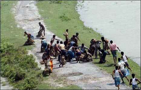 People displaced by floods scramble for relief material dropped on the road by an air force helicopter during rescue operations in Madhepura district
