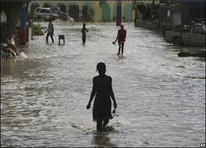 People wade through a flooded street after Tropical Storm Hanna hit Gonaives, Haiti
