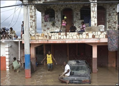People take shelter from a flooded street on the second floor of a home in Gonaives
