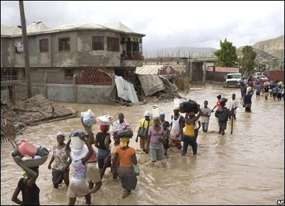 People wade through flooded streets in Gonaives