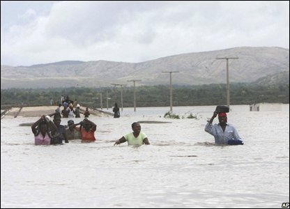 People cross an area flooded by heavy rains in Savan Desole