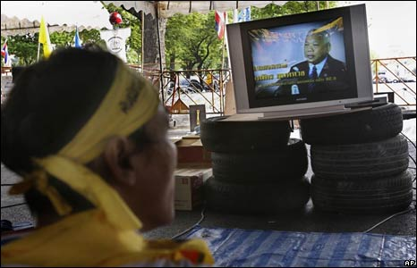 A protester listens as the television broadcasts the prime minister's radio address on 4 September 2008