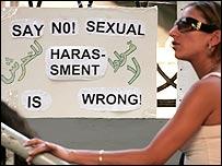 فتاة مصرية وبجانبها  ملصق يدعو الى مكافحة التحرش