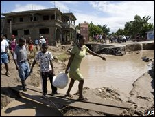Residents walk along a flooded street in Gonaives, Haiti (04/09/2008)
