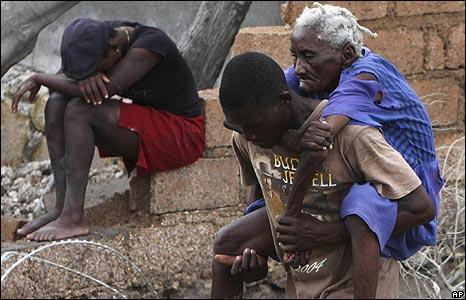 Man carries an elderly woman through Gonaives, Haiti, on 4/9/08