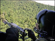 A Philippine Air Force gunner mans a machine gun as a helicopter flies over Lanao del Norte province on 28 August 2008
