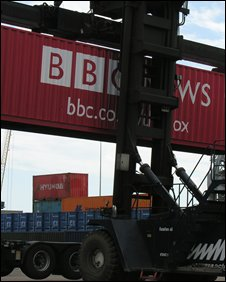 Container with BBC News logo being moved by grab truck