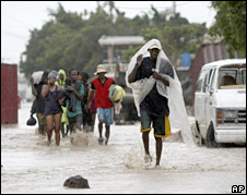 Haitians wade through a flooded street in Gonaives (07/09/08)