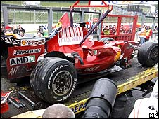 Kimi Raikkonen's Ferrari is carried back to the pits after the Finn's crash on the penultimate lap of the Belgian Grand Prix