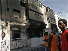 African immigrants outside a burned out house in Almeria, Spain