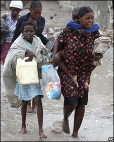 Residents wading through a flooded Gonaives street