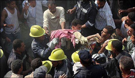 Rescue workers remove the corpse of a child from the rubble in Cairo