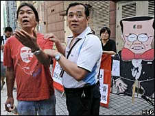 Pro-democracy lawmaker Leung Kwok-hung (L) talks to a policeman as they stand in front of a cut out depicting Chief Executive Donald Tsang on 7 September 2008