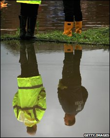 People reflected in flood water, Getty