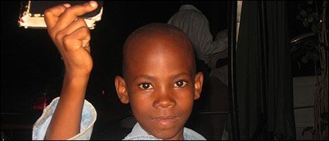 Ugandan boy Muwanguzi Achilewo holding up his Bible