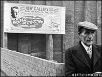 Creyente de la Iglesia Adventista frente a pancarta sobre el fin del mundo.