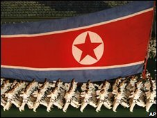 North Koreans march with the national flag in Pyongyang (13 August 2008)