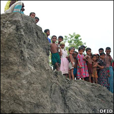Villagers stand on crumbling river bank