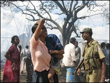 A policeman stands guard as an internally displaced ethnic Tamil woman reacts after seeing her house which was destroyed by a fire at a camp for internally displaced people in Vavuniya - AP