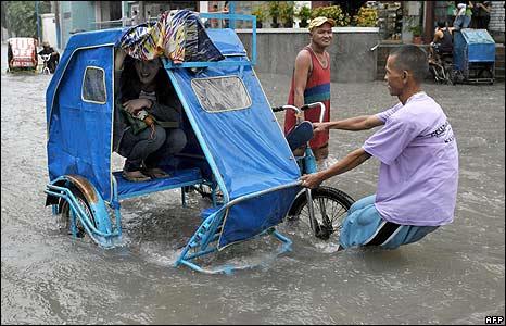 A Filipino man pulls his rickshaw through flood waters in Makati city, Manila