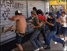 Youths try to kick down shutters on a building in Santa Cruz on 9 Sep