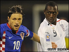 Emile Heskey was booked for a foul on Niko Kovac (l)