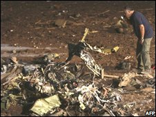 A security agent checks the crash scene of a Cobra helicopter near Afula, Israel, 10 September 2008