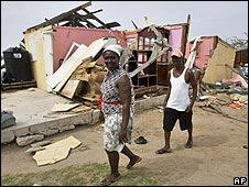 Local residents walk past the damage on Grand Turk in the Turks and Caicos Islands, on 8 September 2008