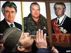 A Serbian Radical Party supporter kissing photos of war crimes suspects Radovan Karadzic (L), Ratko Mladic (C) and Vojislav Seselj