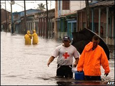 A Red Cross worker helps a man get through flood water in Surgidero de Batabano, Cuba (10/09/2008)