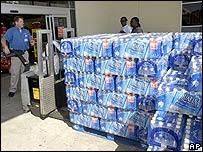 Empleado alcanza botellas de agua para residentes de Texas