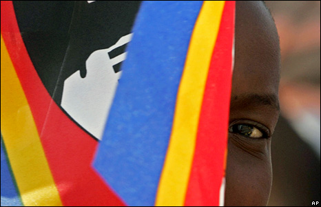 A child peeping from behind a Swazi flag