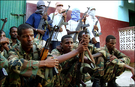 Somali Islamists fighters standing behind crouching government soldiers
