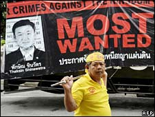 A protester walks past a sign attacking former leader Thaksin Shinawatra on 12 September 2008
