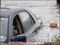 Hombre trata de rescatar su vehículo en Galveston.