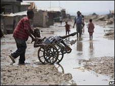 A man on a wheelchair is helped through the mud in Gonaives, Haiti