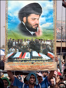 A supporter of Moqtada Sadr holds up a poster of him