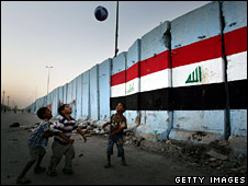 Boys play football near a security barrier in Sadr City