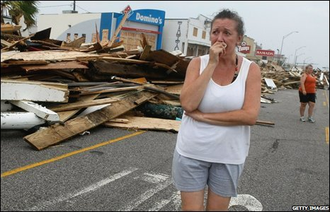 Diane Glowaeki walks among debris on Seawall Boulevard left by Hurricane Ike on 13 September 2008 in Galveston, Texas