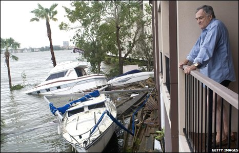 A man looks at the damaged boats resting in the pool area of his town home on 13 September 2008 in Nassau Bay, Texas