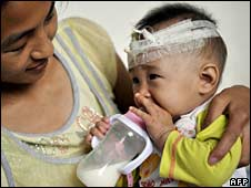 A mother with her baby - who fell ill after consuming contaminated milk - in hospital in Wuhan, Hubei province, on Saturday
