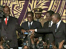 Robert Mugabe (c) shakes hands with Morgan Tsvangirai, Arthur Mutambara and Thabo Mbeki