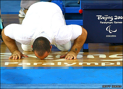 Iraq's Thaer Al-Ali kisses the ground at the Aeronautics and Astronautics Gymnasium