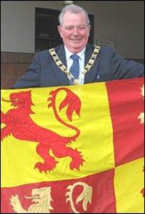 Raymond Bartley, Arweinydd Cyngor Sir Ddinbych, gyda baner Glyndwr