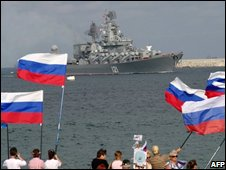 Pro-Russian supporters wave flags as they welcome a Russian warship to the Crimea