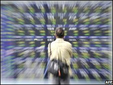 An investor looks at a share prices board in Tokyo on 18 September, 2008