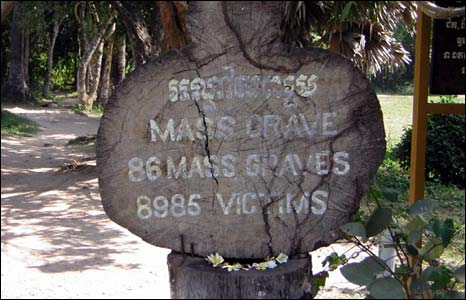 A sign indicates a mass grave at Choeung Ek.