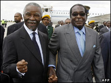 Thabo Mbeki holds the hand of Zimbabwean President Robert Mugabe (R) at Harare airport on 21 July 2008
