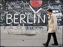 Hombre camina junto a muro de Berlín.