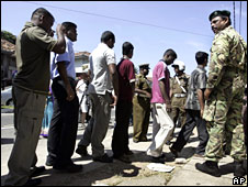 A Sri Lankan police officer stands guard as ethnic Tamil civilians queue up to register their names in Colombo, Sri Lanka